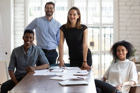 Portrait of confident young happy multiracial business people posing for photo. Successful team of mixed race employees looking at camera. Joyful millennial diverse professionals gathered near table. Foto de archivo