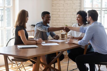Happy multiracial colleagues watching african american male employee shaking hands with teammate at office. Pleasant biracial businessman thanking partner for help or congratulating with success. Stock Photo