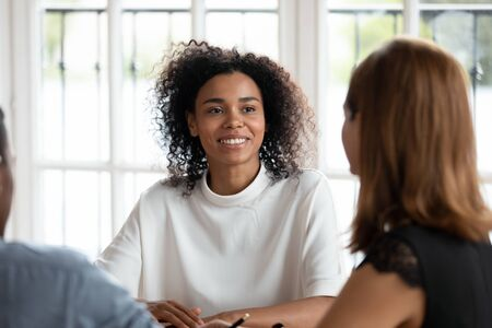 Smiling african american young businesswoman talking with diverse clients or partners at business meeting in office. Happy mixed race female hr manager conducting job interview with applicants.
