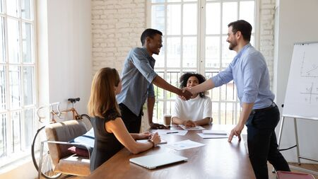 Happy young african ethnicity businessman establishing partnership with confident professional. Happy multiracial colleagues watching boss making agreement with client or praising employee at office.