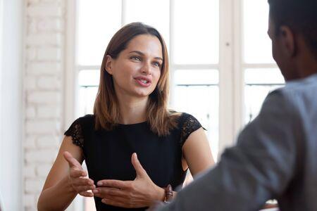 Headshot-Fokus auf glückliche, angenehme junge weibliche Finanzberaterin, Makleranwältin, die Vertragsdetails einem konzentrierten, nachdenklichen afroamerikanischen männlichen Kunden bei einem Treffen im Firmenbüro erklärt.