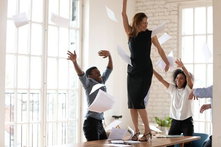 Euphoric young business woman dancing on table, enjoying international company success celebration at office. Overjoyed mixed race colleagues throwing papers, celebrating important achievement.