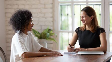Angenehme junge weibliche HR-Managerin, die ein Vorstellungsgespräch mit einer qualifizierten afrikanischen ethnischen Frau hält. Glücklicher Bewerber für gemischte Rassen, der beim Treffen mit dem Arbeitgeber im Firmenbüro einen guten ersten Eindruck macht. Standard-Bild
