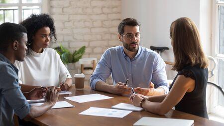 Colegas de etnia africana enfocados viendo a un gerente calificado en anteojos explicando los detalles del contrato a la clienta. Empleados concentrados que escuchan las instrucciones del proyecto del jefe en la oficina. Foto de archivo