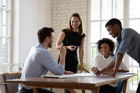 Heureux jeunes collègues multiraciaux s'amusant, écoutant un homme d'affaires joyeux à lunettes lors d'une réunion d'affaires au bureau. Coéquipiers souriants de race mixte discutant d'idées de projets sur le lieu de travail. Banque d'images