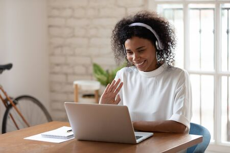 Happy african american young business woman wearing wireless headphones, looking at computer screen, waving hello. Pleasant attractive mixed race female professional holding video call with client.
