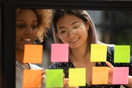 Close up head shot smiling vietnamese female scrum master working together with happy african american business woman partner, organizing IT project working process using glass window kanban board. 写真素材