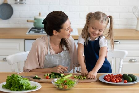 Front view happy young mom watching overjoyed little preschool daughter cropping vegetables on wooden board. Smiling woman teaching small kid girl basics culinary, preparing food together at kitchen.