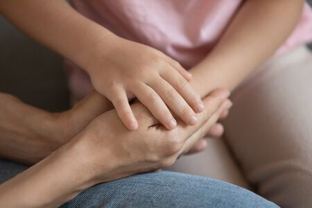 Close up cropped image little daughter putting hand on mommy s hands, demonstrating support and care. Young caring woman joined palms with small kid girl. Symbol of love and family understanding.