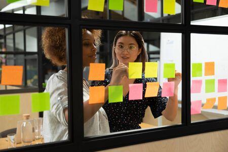 Konzentrierte afroamerikanische junge Scrum-Masterin, die mit einer intelligenten vietnamesischen Geschäftsfrau-Kollegin zusammenarbeitet und Notizen auf klebrigem Papier am Fensterglas-Agilen-Kanban-Board im Büro macht.