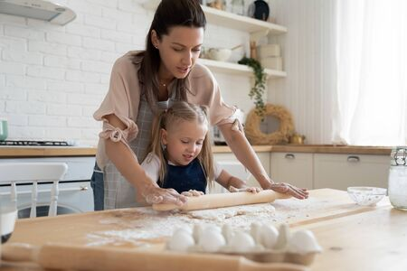 Focused young mother showing adorable preschool daughter how to roll out dough for pizza pie cookies. Little cute kid child in uniform learning muffins bans cooking process with happy mom at kitchen.