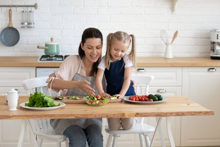 Happy mother sitting at wooden table in kitchen, cuddling little daughter, preparing food in aprons together. Smiling young woman giving first culinary class to interested small child girl at kitchen.
