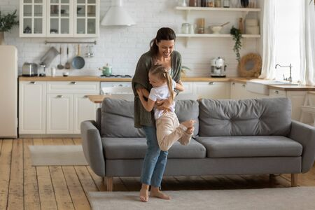 Full length smiling young mother standing on carpet in kitchen studio, lifting happy small cute daughter on hands. Cheerful family of two playing, having fun, enjoying leisure time together at home. Standard-Bild - 133969062