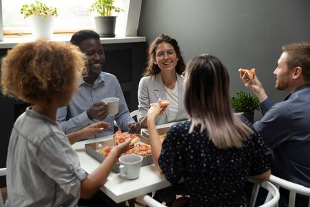 Overjoyed group of mixed race colleagues having fun on friday evening at office. Happy multiracial employees sharing lunch, eating pizza, drinking coffee tea, chatting, laughing together at workplace.