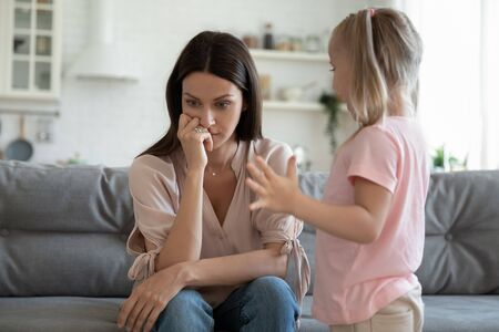 Stressed thoughtful 30s mother ignoring playful happy small daughter. Upset frustrated young woman lost in thoughts, does not pay attention to little preschool kid girl. Family problems concept.