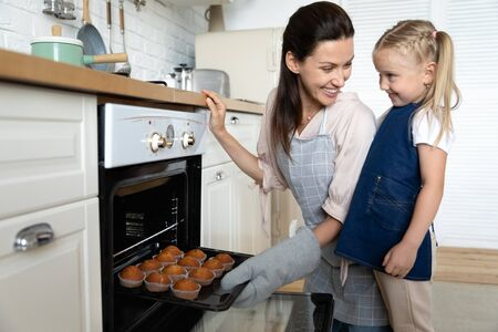 Side view happy young mother taking freshly baked muffins out of oven, showing delicious homemade pastry to little cute smiling daughter helper. Joyful family in aprons satisfied with prepared food.