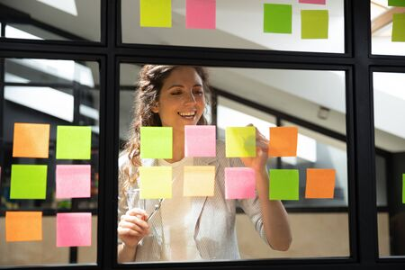 Happy caucasian female scrum master standing near agile kanban method glass window board, writing additional tasks on sticky paper notes, satisfied with start up project working progress at office. 写真素材