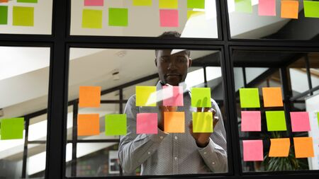Focused millennial african american male manager organizing planning working process of start up business project at glass window agile scrum board, using sticky papers with important notes at office.