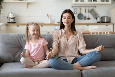 Front view mindful calm 30s woman sitting in lotus pose with cute little daughter on comfortable sofa in living room. Smiling preschool girl practicing yoga breathing exercises with mommy at home.