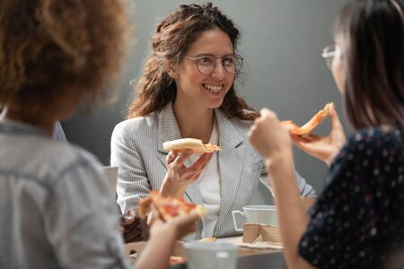 Head shot sincere overjoyed beautiful caucasian manager sharing lunch with mixed race teammates. Multiracial colleagues chatting, enjoying break or relaxing after hard working week together at office.