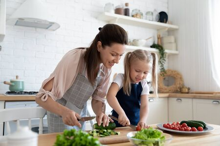 Young mother watching little daughter cutting fresh vegetables on wooden board. Smiling mommy teaching small adorable kid girl preparing food at kitchen. Happy family in aprons cooking together. Stock Photo