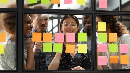 Grupo de jóvenes gerentes interesados de raza mixta reuniéndose cerca del líder del equipo vietnamita sonriente, escribiendo detalles del proyecto de inicio o tareas en coloridas notas adhesivas, utilizando la metodología kanban scrum en la oficina.