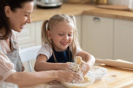 Head shot close up overjoyed little adorable daughter helping smiling young mother kneading dough by hands in bowl. Happy family in aprons enjoying pancakes bans pie cooking process at kitchen. Stock fotó