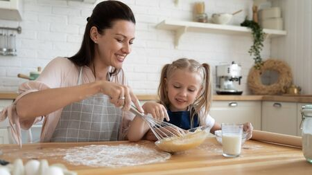 Head shot happy little child girl in flour watching young mommy stirring eggs for homemade pastry. Joyful family in aprons cooking pie at kitchen. Smiling mom giving culinary class to small daughter.