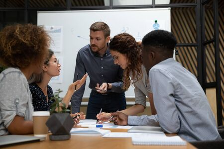 Busy millennial group of motivated mixed race teammates leaning over table at boardroom, discussing first startup project results, negotiating business development marketing strategy together.