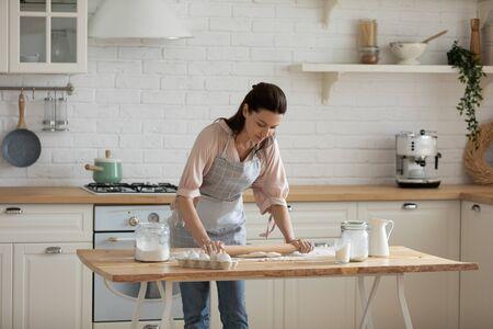 Mujer de 30 años ocupada concentrada inclinada sobre la mesa, extendiendo la masa para pastelería casera. Confitero profesional femenino agradable centrado que hace pedidos de hornear de los clientes, preparando la comida en la cocina en casa.