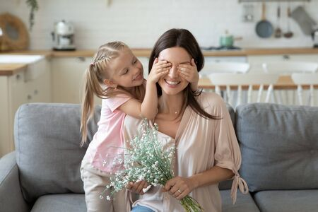 Head shot little girl covering eyes of smiling young mother, sitting on cozy couch with bouquet of field spring flowers. Cute small daughter prepared surprise for happy mom, life events celebration.