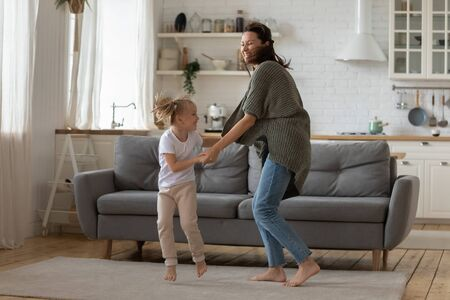 Full length overjoyed family of two having fun at studio kitchen, Happy little preschool child girl holding mommy s hands, dancing to favorite music, jumping, enjoying free time together at home. Stock fotó