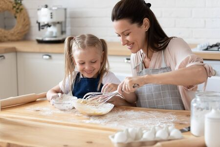 Head shot smiling young mommy showing small preschool daughter how to stir eggs with flour, sitting together in aprons at wooden table. Happy family cooking pastry, homemade cookies at kitchen.