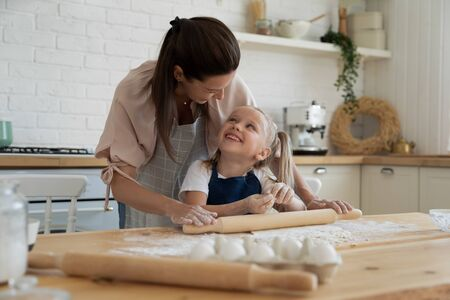Happy cute little preschool daughter enjoying helping smiling mother preparing homemade pastry at kitchen. Smiling small kid girl likes rolling out dough, looking at joyful proud young mom in apron.