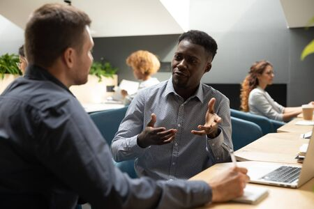 Handsome african american young businessman making business startup offer to confident caucasian investor at meeting in moder coworking space. Multiracial male colleagues discussing project ideas.