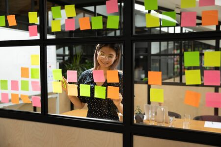 Smiling asian female project manager in eyewear organizing working process at glass window kanban board. Happy vietnamese employee adding paper stickers with tasks, improving managing ideas at office. Stockfoto