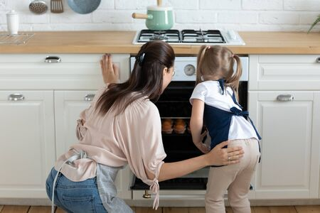 Back rear view young mommy and curious little kid girl wearing aprons, looking into oven, checking if muffins ready to eat. Happy family enjoying pastry cooking process together at modern kitchen.