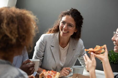 Head shot millennial smiling caucasian business woman listening to colleagues joke, enjoying pizza together on friday evening at workplace. Happy young team leader communicating with teammates.