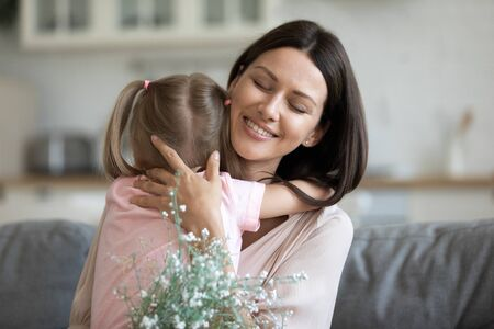Head shot smiling proud 30s mother cuddling little cute daughter, feeling grateful for prepared flowers and birthday wishes. Young woman embracing small kid girl. Family events celebration concept. Standard-Bild - 133969298
