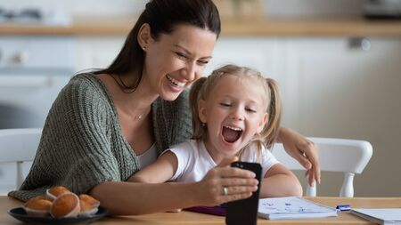 Head shot smiling young mother showing funny cartoons to overjoyed little adorable girl on smartphone. Happy 30s woman recording family video with laughing small preschool daughter on mobile phone. Stock fotó