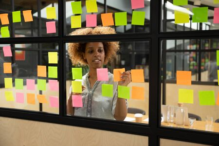 Head shot pleasant concentrated millennial african american female manager planning project workflow, putting paper stickers with tasks on window glass kanban brainstorming board at modern office.