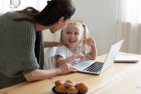 Young mother controlling little kid computer usage, internet web surfing. Happy small child girl watching funny cartoons. Mommy teaching daughter using educational applications software on laptop.