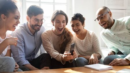 Overjoyed young mixed race friends watching funny video content on smartphone. Happy excited multiracial people having fun at home. Crazy millennial diverse classmates enjoying spending time together.