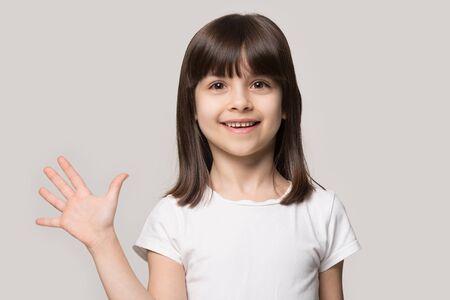 Close up colpo alla testa ritratto con divertente attraente piccola ragazza dai capelli castani. Concetto di attività felice bambino giocoso dà gesto di benvenuto su sfondo grigio, bambino di sei anni che guarda l'obbiettivo e posa. Archivio Fotografico