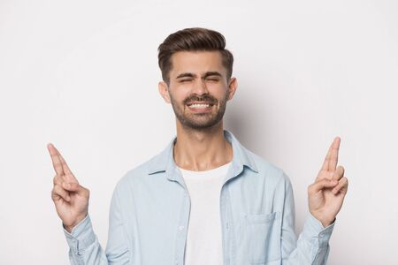 Close up head shot image of happy smiling handsome bearded college guy making wish with closed eyes. Young positive student crossed fingers and optimistic believes in luck and dream on gray background Stockfoto