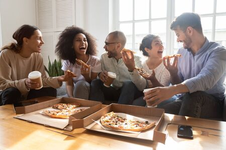 Excited multiracial friends having fun together at home. Happy mixed race young colleagues enjoying eating ordered pizza from cardboard box, chatting, communicating, laughing at jokes on party.