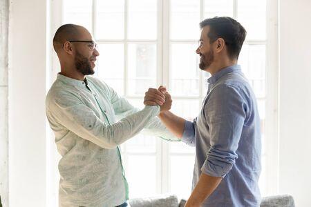 Seitenansicht aufgeregt gemischte männliche Freunde in Brillen, die sich die Hände schütteln. Glückliche beste Freunde, die sich bei einem plötzlichen Treffen begrüßen. Lächelnde Kollegen, die hallo sagen und drinnen miteinander kommunizieren. Standard-Bild