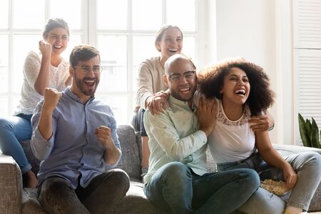 Overjoyed young mixed race people supporting favorite team, sitting together on sofa at home. Excited euphoric multiracial best friends celebrating goal, watching football match on television.