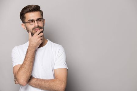 Close up head shot image of suspicious handsome bearded man looking at copy space for ad presentation. Young student with eyewear is in dilemma holding chin and thinking about solution.
