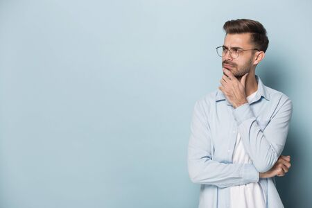 Close up head shot image of pensive handsome bearded man with glasses looks at copy space for texting. Millennial young businessman with eyewear is in dilemma and thinking about solution.